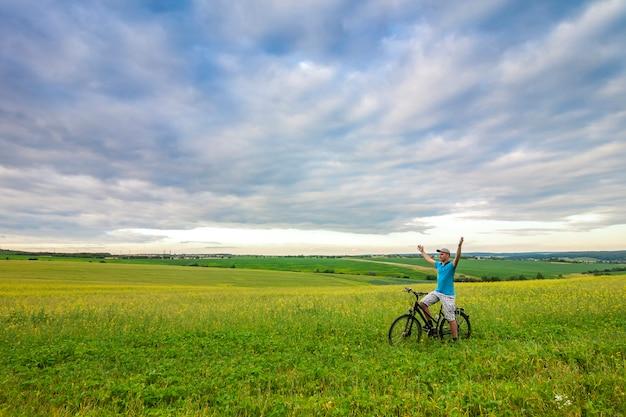 Junger mann mit einem fahrrad auf grünem feld an einem sonnigen sommertag