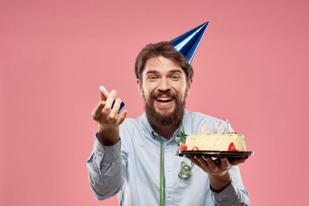 Junger mann mit einem festlichen kuchen mit scheiben feiert einen geburtstag in einer kappe, isolation und quarantäne