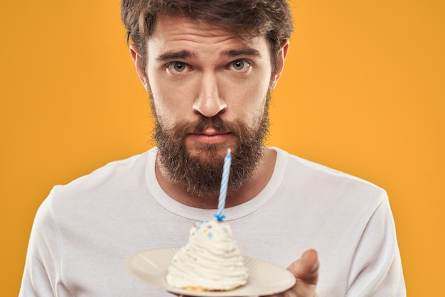 Junger mann mit einem festlichen kuchen mit scheiben feiert einen geburtstag in einer kappe