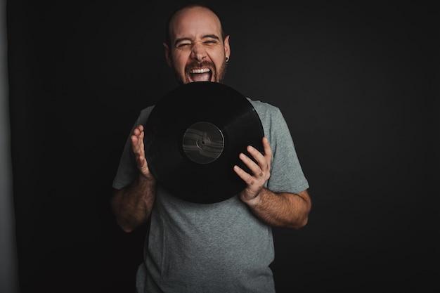 Junger mann mit einem glücklichen ausdruck, der ein vinyl unter den lichtern vor einem dunklen hintergrund hält