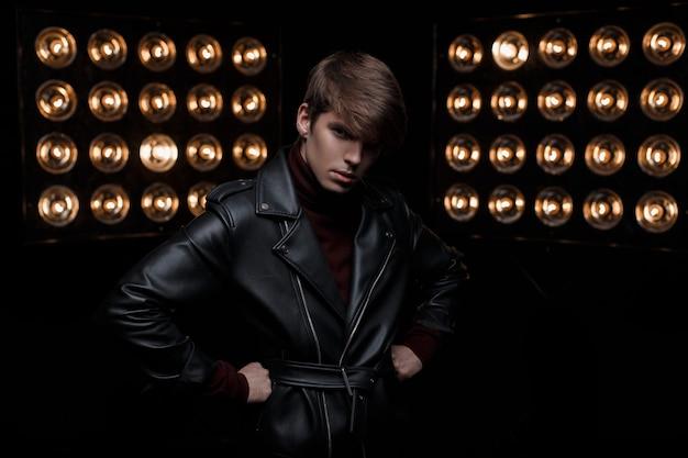 Junger mann mit einem haarschnitt in einer lederjacke im retro-stil im burgunder-golf steht und schaut auf die kamera im studio vor dem hintergrund der hellen professionellen vintage-lampe. stilvoller kerl