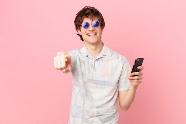 Junger mann mit einem handy, das auf kamera zeigt, die sie wählt