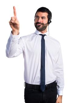 Junger mann mit einem headset berühren auf transparenten bildschirm