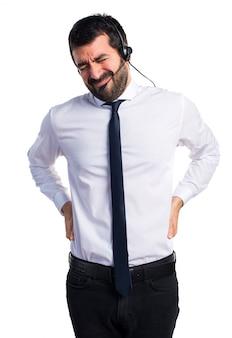 Junger mann mit einem headset mit rückenschmerzen