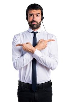 Junger mann mit einem headset zeigt auf die seiten mit zweifeln