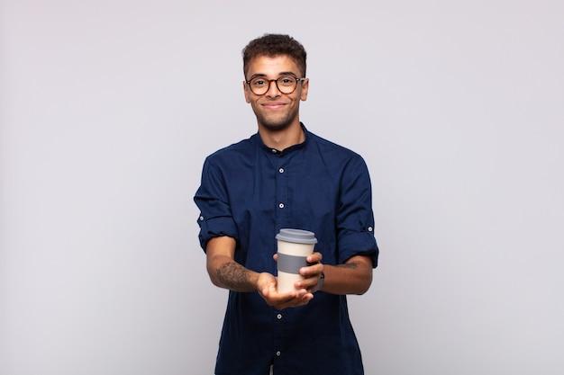 Junger mann mit einem kaffee, der glücklich mit freundlichem, selbstbewusstem, positivem blick lächelt und ein objekt oder konzept anbietet und zeigt
