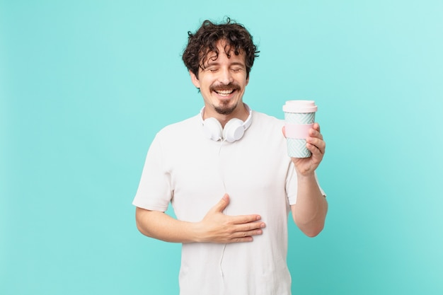 Junger mann mit einem kaffee, der laut über einen lustigen witz lacht