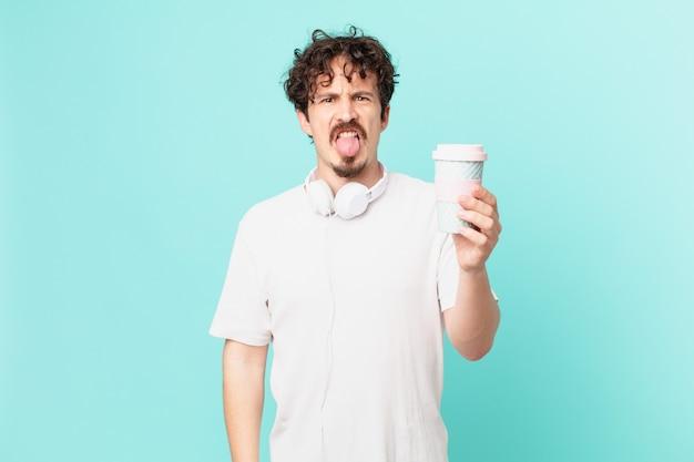 Junger mann mit einem kaffee, der sich angewidert und gereizt fühlt und die zunge herausstreckt
