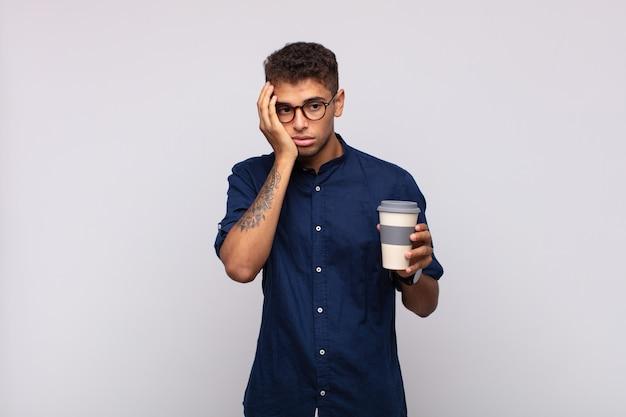 Junger mann mit einem kaffee, der sich nach einer ermüdenden, langweiligen und mühsamen aufgabe gelangweilt, frustriert und schläfrig fühlt und das gesicht mit der hand hält