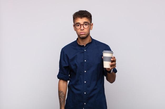 Junger mann mit einem kaffee, der traurig und weinerlich mit einem unglücklichen blick ist und mit einer negativen und frustrierten einstellung weint