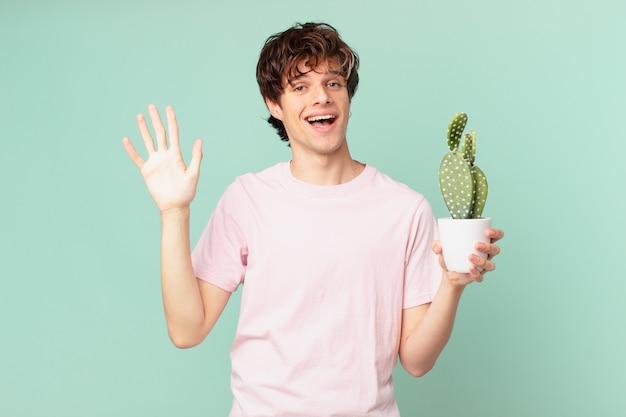 Junger mann mit einem kaktus, der glücklich lächelt, die hand winkt, sie begrüßt und begrüßt