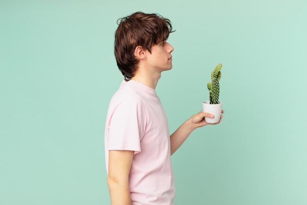 Junger mann mit einem kaktus in der profilansicht, der nachdenkt, sich vorstellt oder träumt