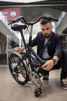 Junger mann mit einem klapprad in der stadt