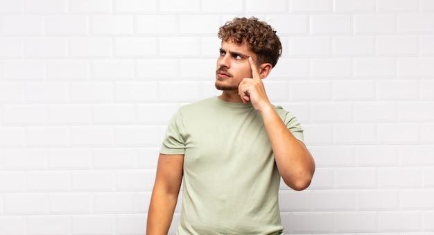Junger mann mit einem konzentrierten blick, der sich mit einem zweifelhaften ausdruck isoliert wundert