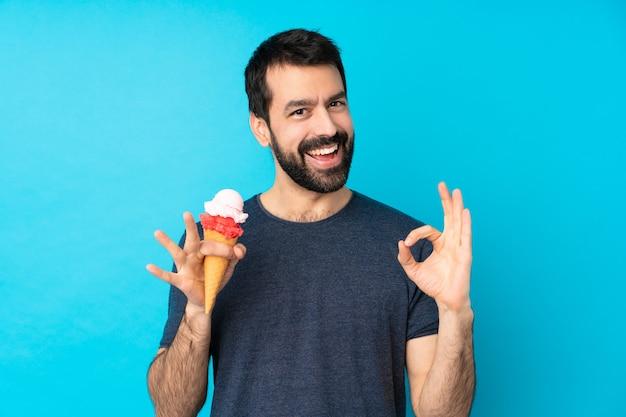 Junger mann mit einem kornetteis über blau, das ein ok-zeichen mit den fingern zeigt