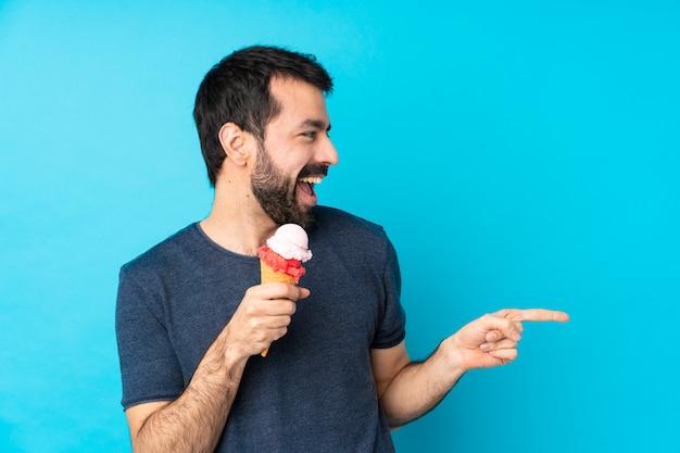 Junger mann mit einem kornetteis über blau zeigendem finger zur seite und präsentiert ein produkt