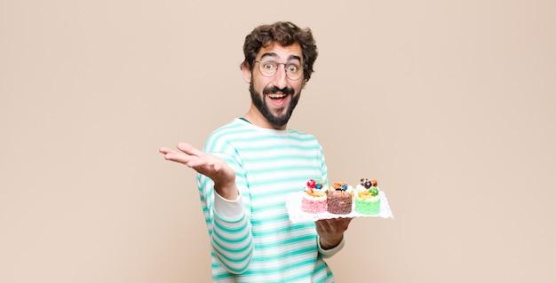 Junger mann mit einem kuchen gegen flache wand