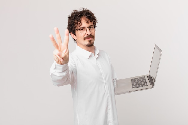 Junger mann mit einem laptop, der lächelt und freundlich aussieht und nummer drei zeigt