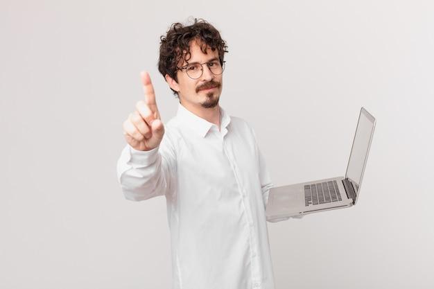 Junger mann mit einem laptop, der lächelt und freundlich aussieht und nummer eins zeigt
