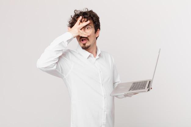 Junger mann mit einem laptop, der schockiert, verängstigt oder verängstigt aussieht und das gesicht mit der hand bedeckt