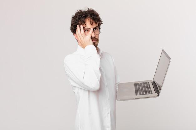 Junger mann mit einem laptop, der sich nach einem ermüdenden gefühl gelangweilt, frustriert und schläfrig fühlt