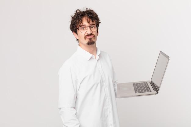 Junger mann mit einem laptop, der traurig und weinerlich mit einem unglücklichen blick und weinen ist