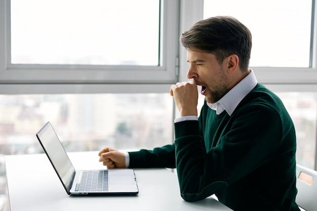 Junger mann mit einem laptop im geschäftsanzug, der im büro und zu hause arbeitet