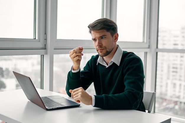 Junger mann mit einem laptop in einem geschäftsanzug, der im büro arbeitet