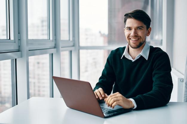 Junger mann mit einem laptop in einem geschäftsanzug, der im büro und zu hause auf dem hintergrund eines fensters arbeitet und online interviewt