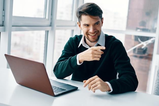 Junger mann mit einem laptop in einem geschäftsanzug, der raumraum und zu hause auf dem raum eines fensters arbeitet, online interviewend