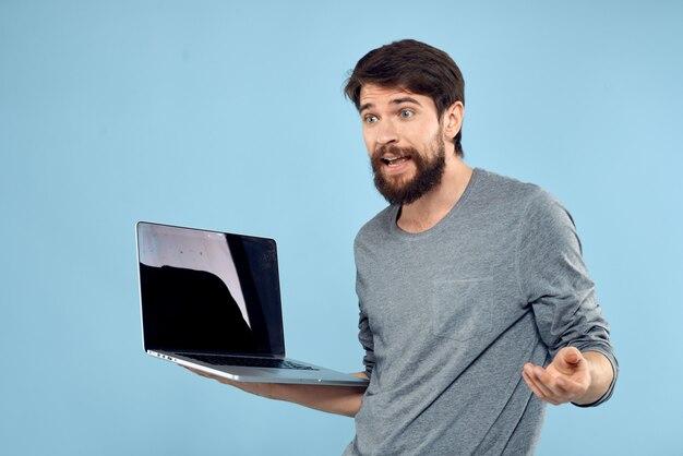 Junger mann mit einem laptop in seinen händen auf hellblauem emotionalem aufstellen