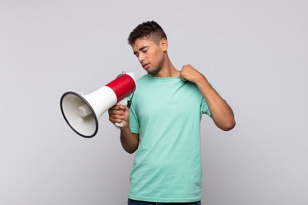 Junger mann mit einem megaphon, das sich gestresst, ängstlich, müde und frustriert fühlt, hemdhals zieht und mit problem frustriert aussieht