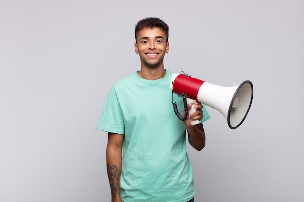Junger mann mit einem megaphon, der glücklich mit einer hand auf hüfte und selbstbewusster, positiver, stolzer und freundlicher haltung lächelt