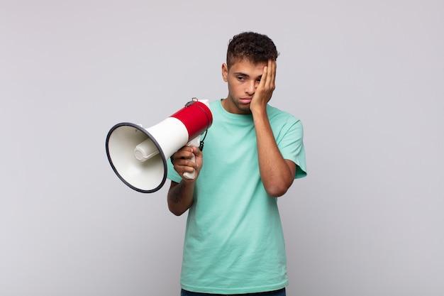Junger mann mit einem megaphon, der sich nach einer lästigen, langweiligen und mühsamen aufgabe gelangweilt, frustriert und schläfrig fühlt und das gesicht mit der hand hält
