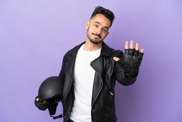 Junger mann mit einem motorradhelm auf lila hintergrund isoliert, der fünf mit den fingern zählt
