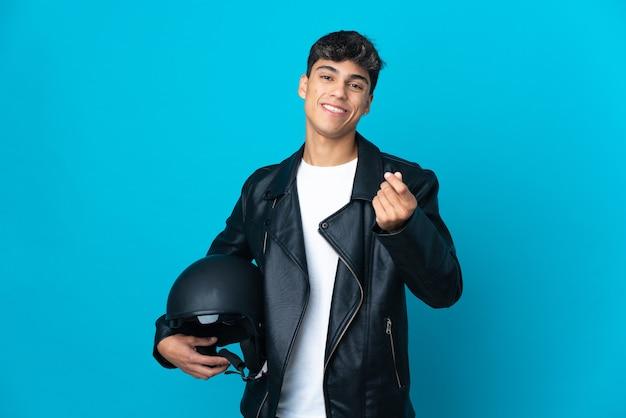 Junger mann mit einem motorradhelm auf lokalisiertem blau, das geldgeste macht