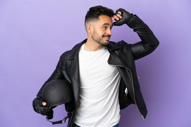 Junger mann mit einem motorradhelm, der auf lila hintergrund isoliert ist, lächelt viel