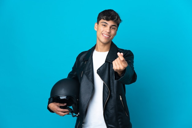 Junger mann mit einem motorradhelm über blau, der geldgeste macht