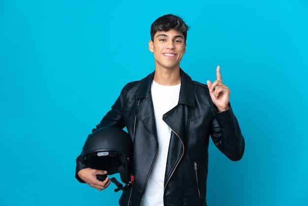 Junger mann mit einem motorradhelm über isoliertem blau, das einen finger im zeichen des besten zeigt und hebt