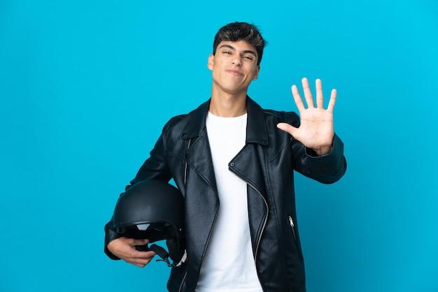 Junger mann mit einem motorradhelm über isoliertem blau, das fünf mit den fingern zählt