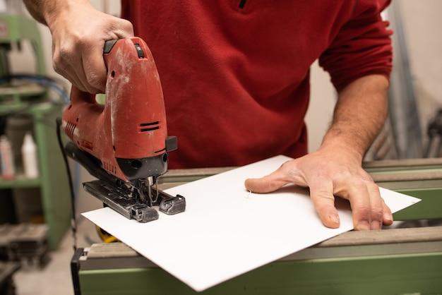 Junger mann mit einem roten pullover, der etwas mit industriewerkzeugen macht