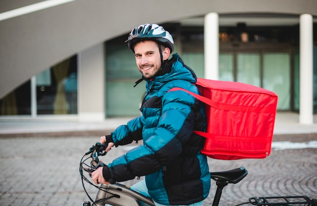 Junger mann mit einem rucksack für lebensmittellieferung und einem fahrradschutzhelm. hausaufgaben, radtour, pizza lieferung