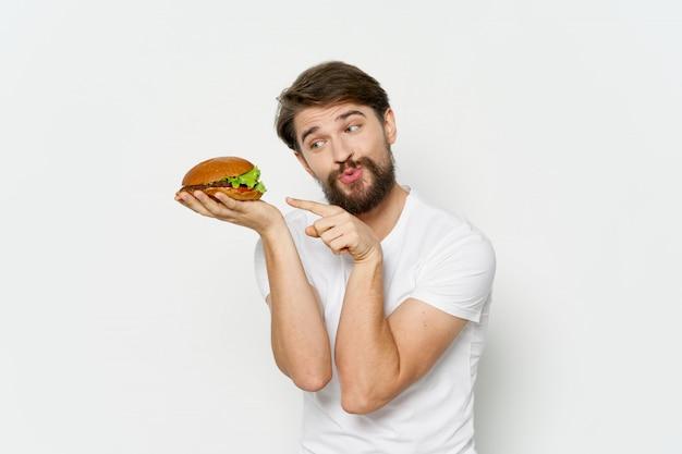 Junger mann mit einem saftigen hamburger in den händen, ein mann, der einen burger isst