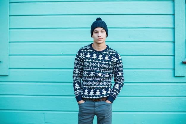 Junger mann mit einem schönen lächeln in einer strickmütze mit blauen augen in einem blauen weihnachtsweinlesepullover in jeans steht in der stadt nahe einem hellblauen holzhaus. charmanter kerl.