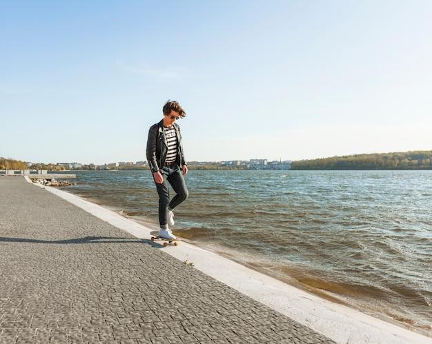Junger mann mit einem skateboard nahe dem meer