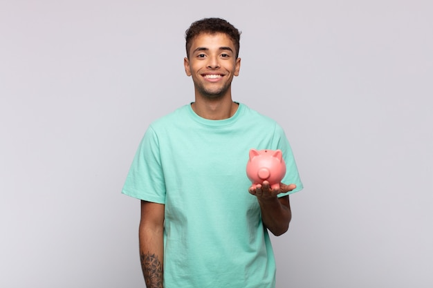 Junger mann mit einem sparschwein, der glücklich mit einer hand auf der hüfte und selbstbewusster, positiver, stolzer und freundlicher haltung lächelt