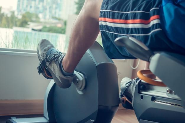 Junger mann mit einem spinning-bike in einem indoor-fitnesscenter