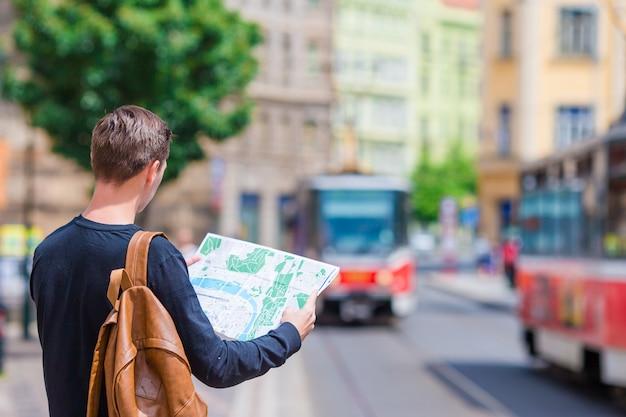 Junger mann mit einem stadtplan und einem rucksack in europa