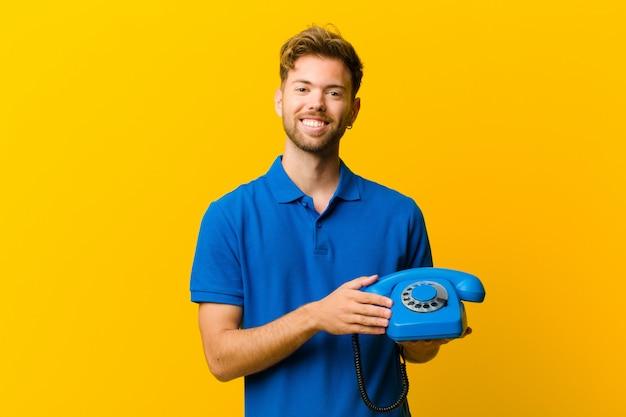 Junger mann mit einem telefon gegen orange hintergrund
