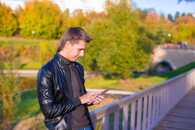 Junger mann mit einem telefon im park